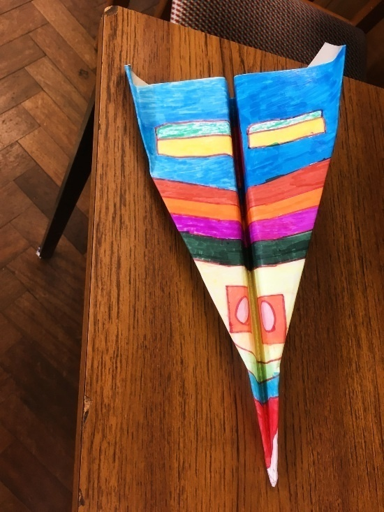 a large and colourful paper airplane on a table