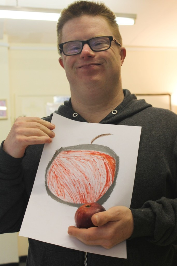 a man is holding his drawing of an apple and the red apple he drew