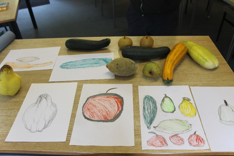 a table with autumn fruit and veg and the pictures / drawings they have inspired