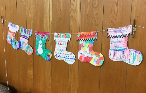 drawn and colourful christmas stockings hanging on a string