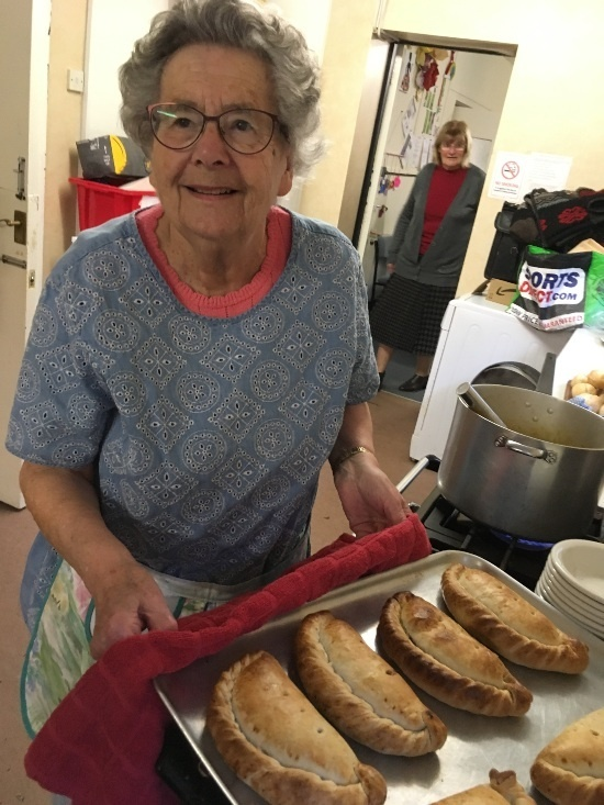 An old woman is in the kitchen with a hot tray of pasties