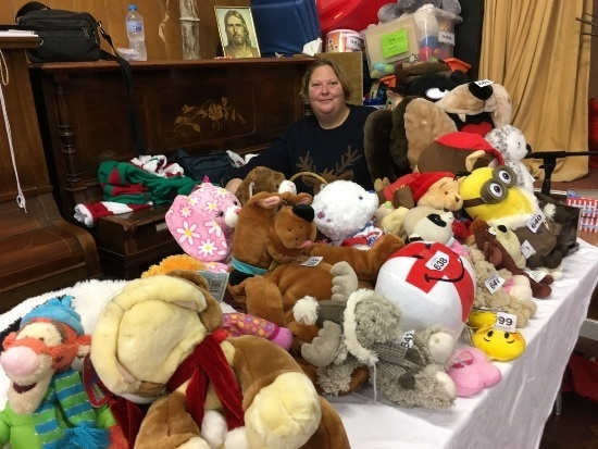 a table of cuddly toys and a lady smiles behind them