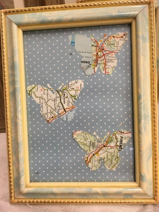 a picture frame with a light blue background with whites dots. 3 butterfly shapes cut out of maps are in the picture frame
