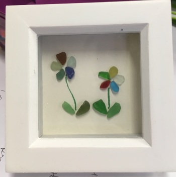 two flowers made out of found pieces of coloured glass are in a square white frame