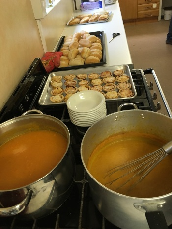 pans of soup on a stove, next to a pile of bowls and a tray of mince pies with bread rolls in the background