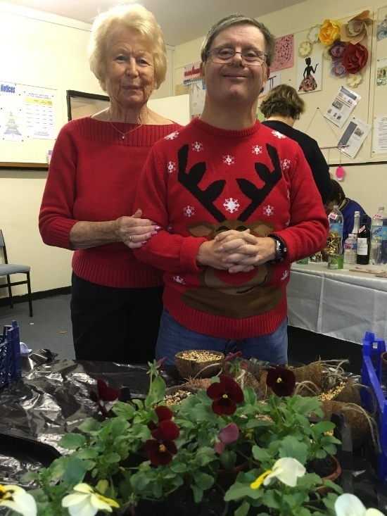 a man and a woman in red jumpers looking at the camera and smiling. The man's red jumper has a image of Rudolf the reindeer onit