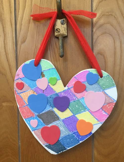 A multi-coloured paper heart hanging from a red ribbon