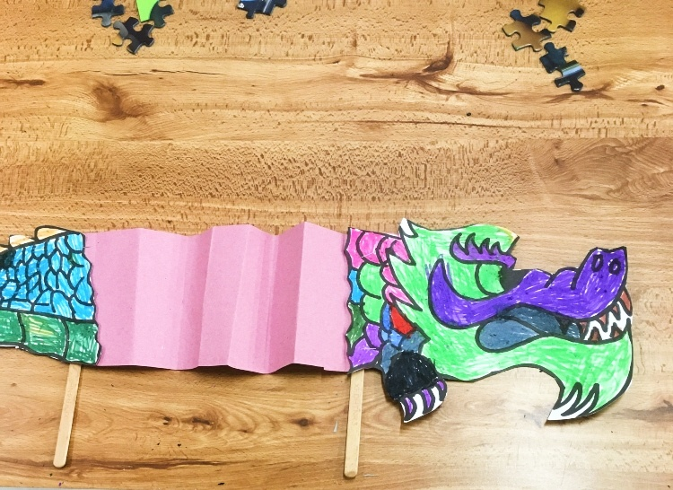a chinese dragon made of paper with a pink crepe paper middle and sticks at the bottom