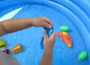 La joacă în piscină cu pistoale cu apă și bucăți de gheață colorată