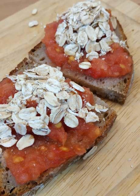 Tostada de pan de centeno con tomate fresco rallado y copos de Avena