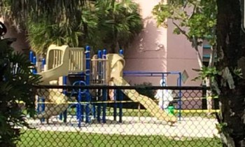 A person in a hazmat suit spraying the playground at Eagle Ridge Elementary School. Photo by William Schedneck.