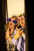 Friends and Family Taking Photos in the Wedding Photo Booth with Over Sized Glasses
