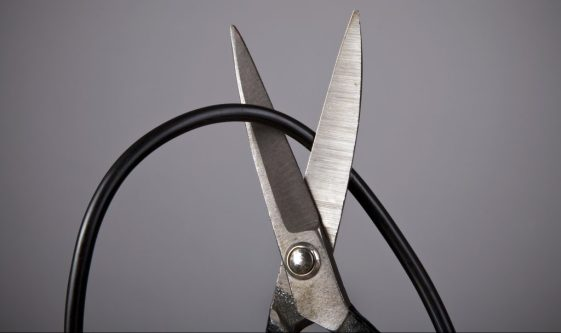 Scissors cutting a computer wire on gray background (wireless or blackout concept)