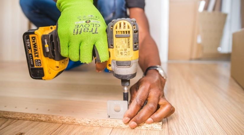 A person using best cordless hammer drill on a brown board