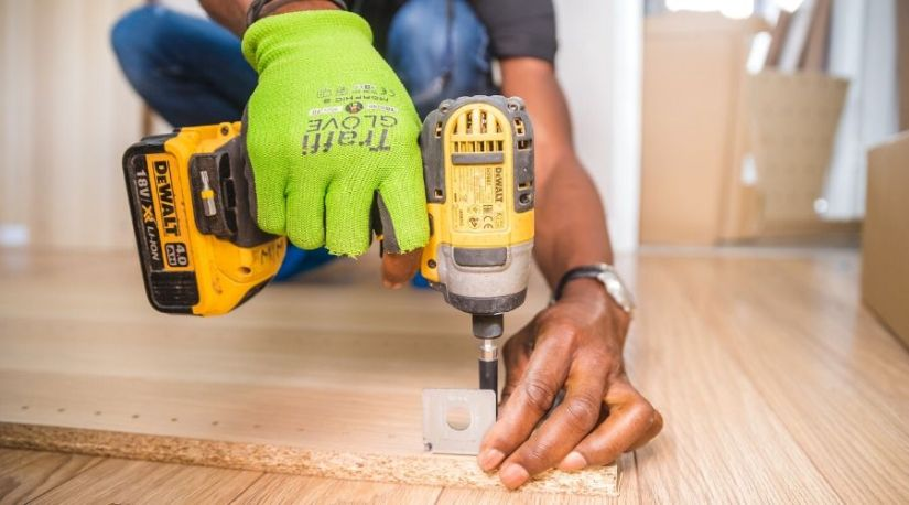 A person using best 1/2 cordless impact on a brown board