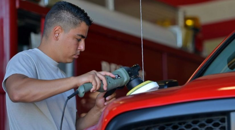 A person using the best cordless car buffer to polish a car affected by fire