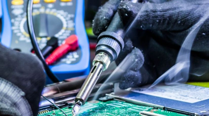 A person using the best cordless soldering iron to solder on a mother-board