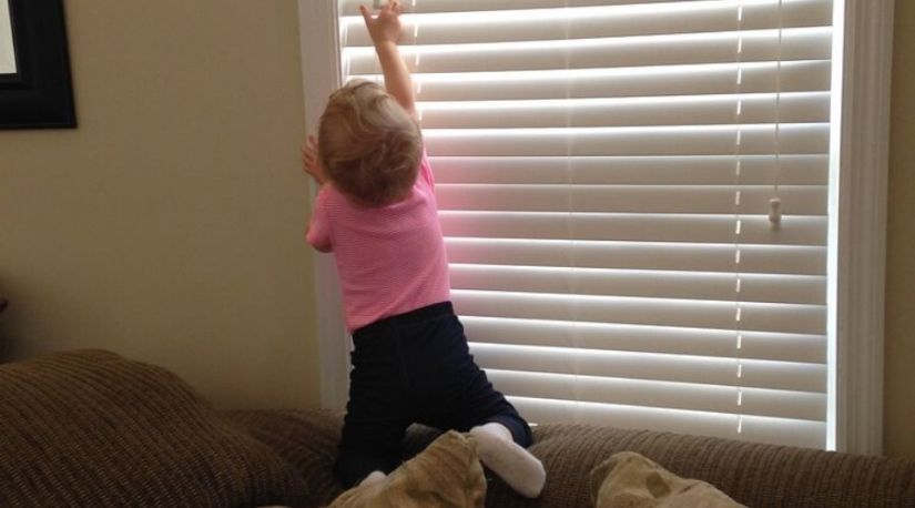 can you shorten cordless blind? Yes, the photo shows a child adjusting a blind to control the light in the room. The blind has been shortened to fit in the desired window space
