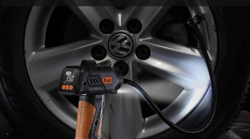 a picture of the best cordless tire inflator in use to inflate a car tire