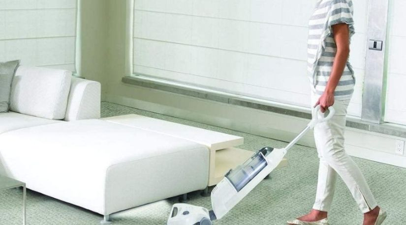 A lady using the best cordless stick vacuum to clean carpet floor