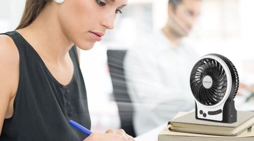 An image of a lady using OPOLAR Mini Portable Battery Operated Handheld Fan for Desk one of the best cordless fan models during her studies