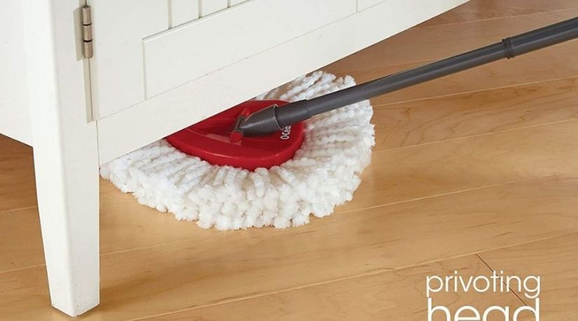 A person using O-Cedar EasyWring Microfiber Spin Mop, one of the best cordless mop for tiles to clean, a tilled floor