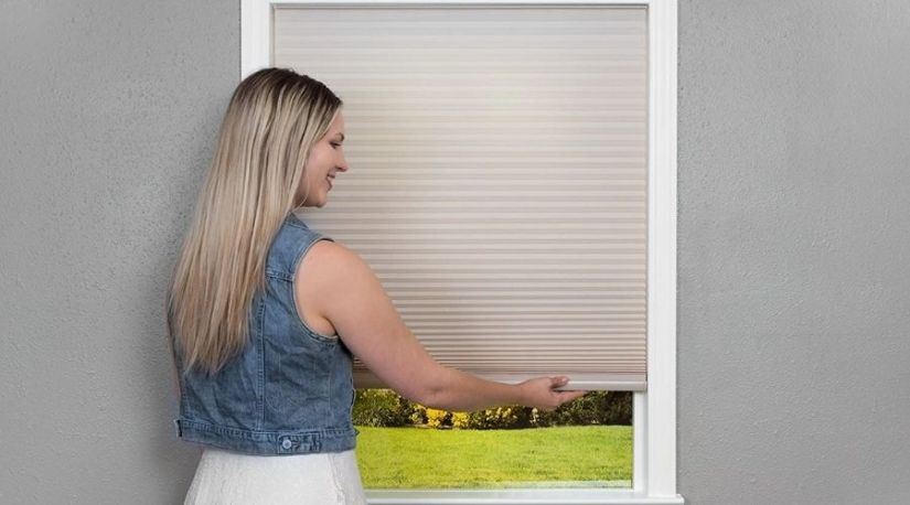 An image of a lady rolling down edi Shade 3512158 Trim-at-Home Light Filtering Fabric Natural, an example of the best cordless blind to control lighting in a room