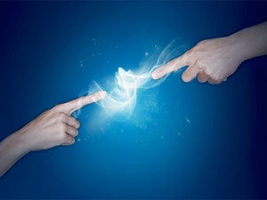 two hands pointing at each other creating an electrical charge against blue background