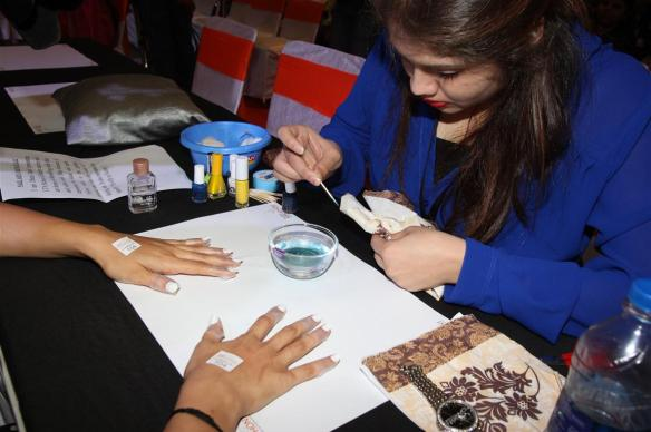 Contestant performing nail art on a model