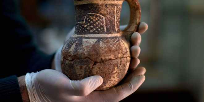A Syrian archeologist holds an artifact that was transported to Damascus for safe-keeping during the Syrian Civil War. AP Photo/Hassan Ammar