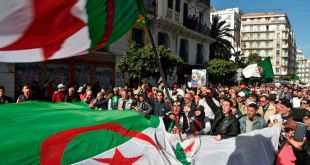 Algerian protesters wave the national flag during a demonstration in the capital Algiers. Photo by Ryad Kramdi/AFP via Getty Images