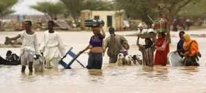 Sudanese people carry their belongings through the flood waters. Isam Al-Haj/AFP via Getty Images
