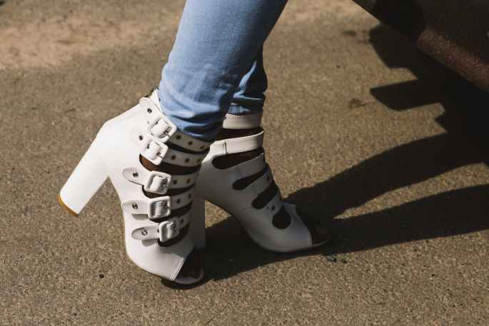 person showing pair of white peep toe chunky heel sandals