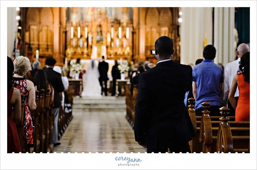 guest standing in aisle to take a picture during wedding ceremony in cleveland