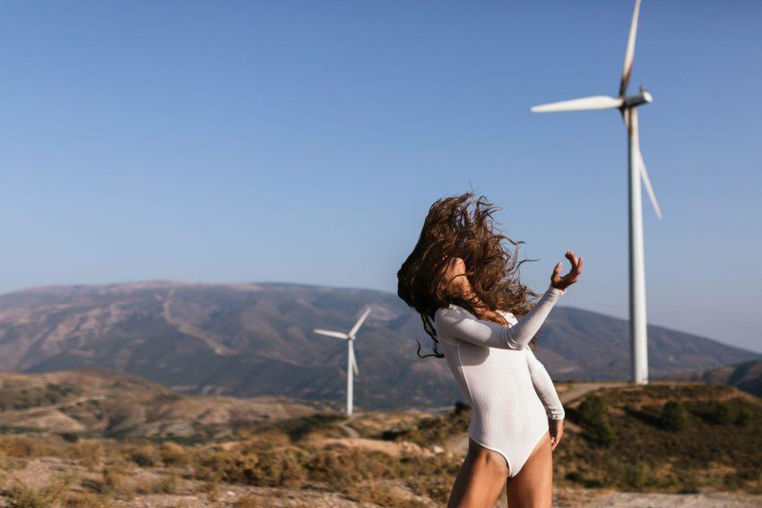 Tender female dancing alone near wind farm on sunny field