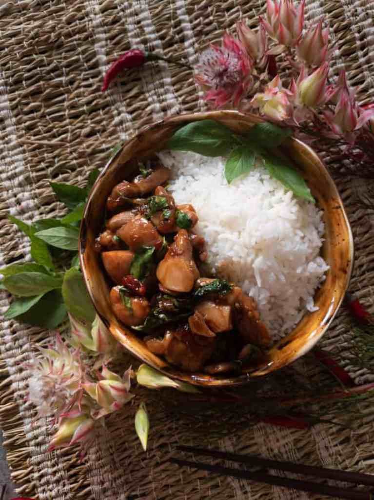 Thai basil chicken served in a bowl with a side of jasmine rice.