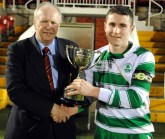 Martin Conlon (Cork AUL) presents the Saxone Cup to Cloughduv Celtic's captain William Buckley after his side's 2-0 victory over CFC Banteer at the Cross last night. Barry Peelo.