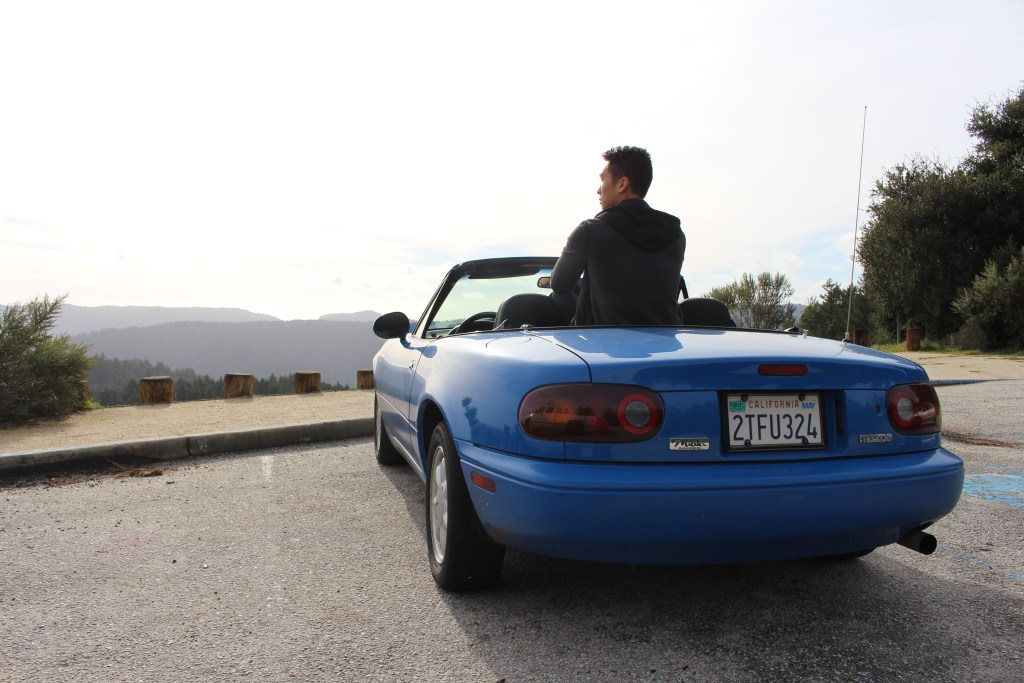Michael sits with his Miata at the Route 9 scenic overlook
