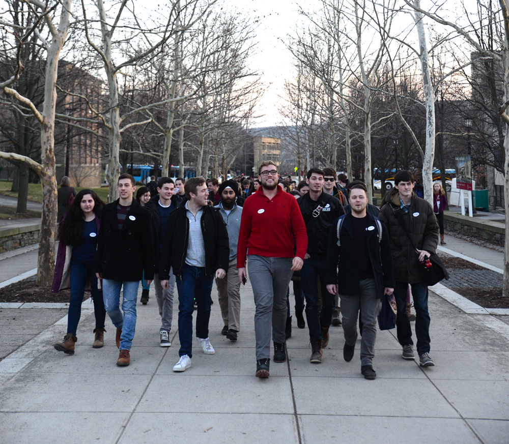 Colton Haney '17 leads a group of hotel students, walking from Statler Auditorium to Williard Straight Hall to express their concerns above the new College of Business.