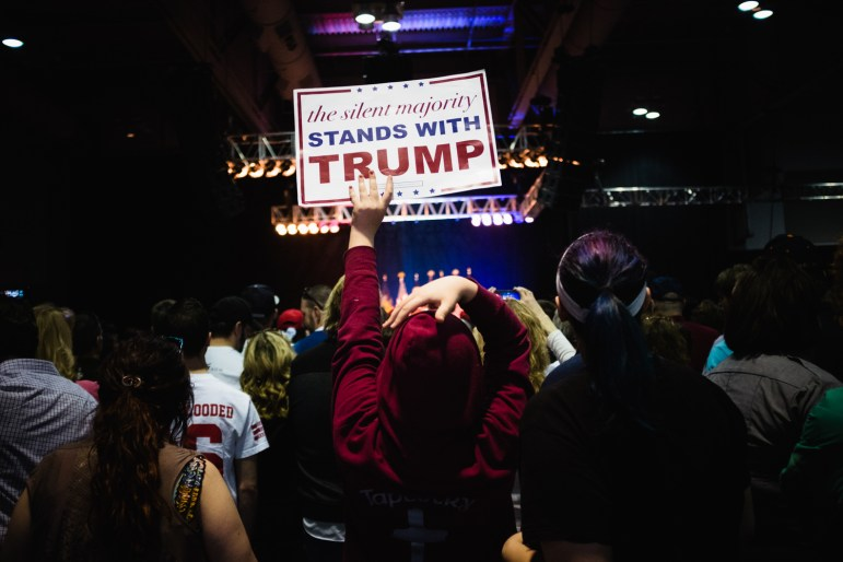 Supporters hoist signs at a Donald Trump rally in Syracuse.