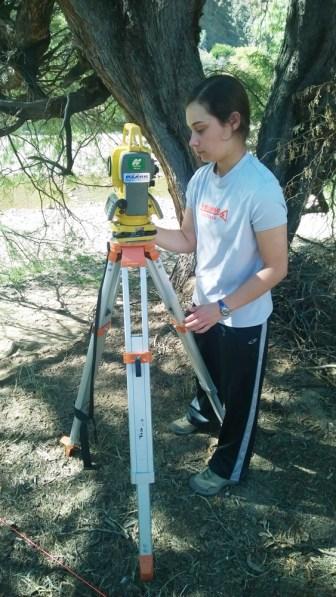 Team Member Surveying Land for Bridge Construction