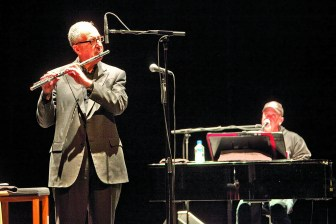 President David Skorton joins Billy Joel on stage in Barton Hall on Dec. 2, 2011 to showcase his jazz flute skills.