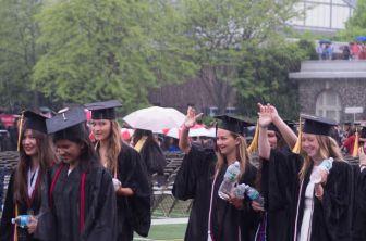 Graduates brave the rain at commencement Sunday.