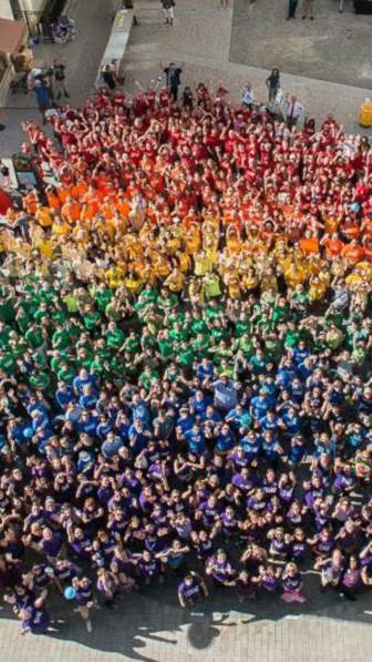 """""""Ithaca is Love"""" attendees pose for a photo Thursday, arranged to form a rainbow in the Commons."""