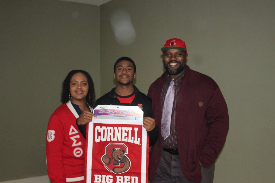 Brendon Gauthier stands holding a Cornell banner next to his mother and step-father.