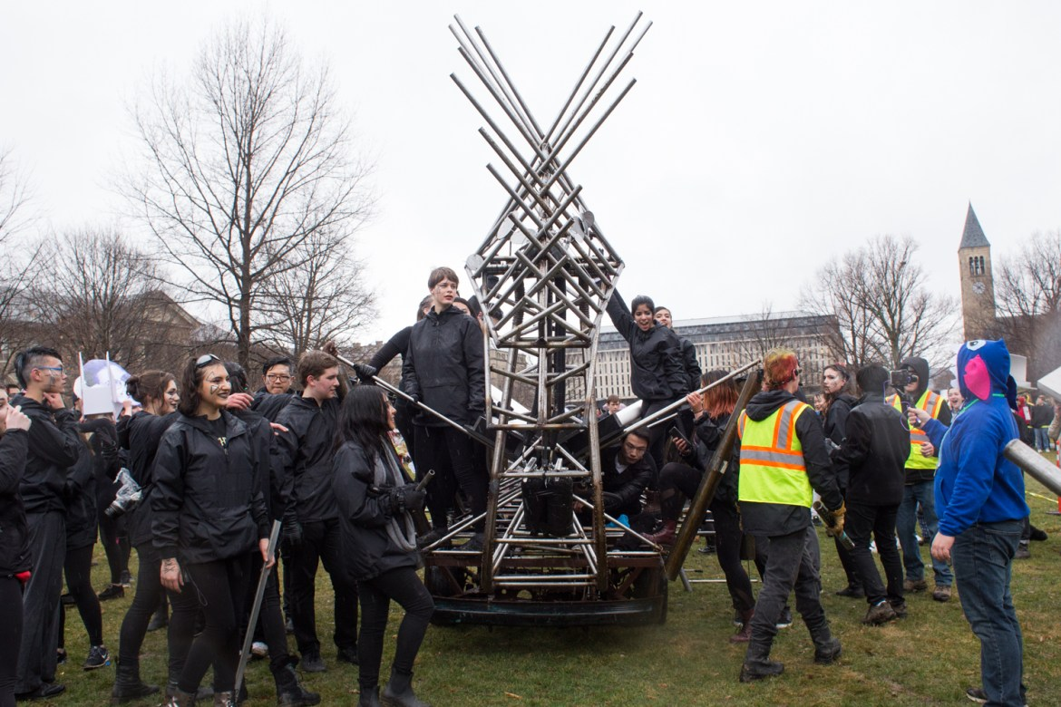 Hundreds of students marched along the 116th Dragon Day parade route on Friday, chanting and banging on the creation with metal rods.