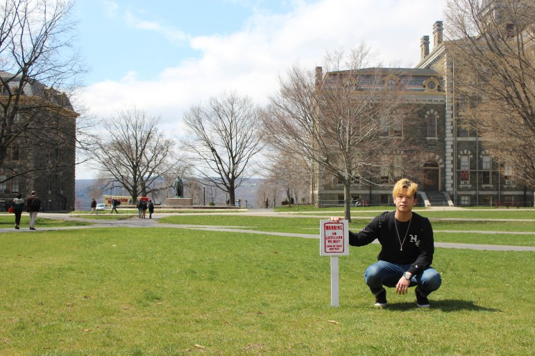 """Daniel Seung Hwan Lee '20 crouches next to his art installation, the """"Cornell Beach,"""" after the other sign he created was swiped earlier in April."""