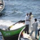 Fishermen inspect monofilament fishing lines on Lake Victoria's shore.