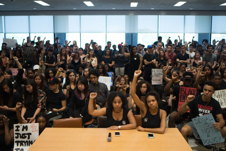 Traci Celestin and Delmar Fears, co-chairs of Black Students United, sit in silence and hold up their fists at a University Assembly meeting in Clark Hall, September 19th, 2017. (Cameron Pollack / Sun Photography Editor)