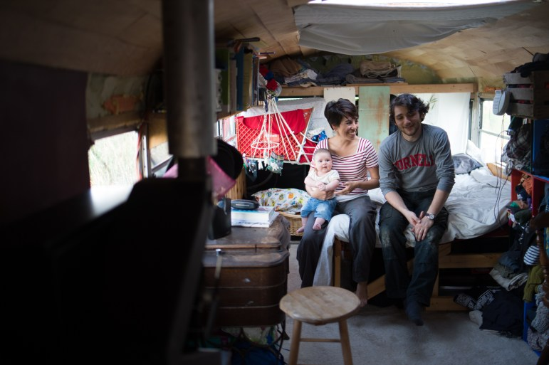 Eli Shanks '17 poses with his partner Andrea Reyes and his son Rafael in their school bus-turned-home in Trumansburg, New York, September 17th, 2017. (Cameron Pollack / Sun Photography Editor)